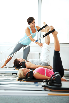 Coach helping people with Pilates exercises.